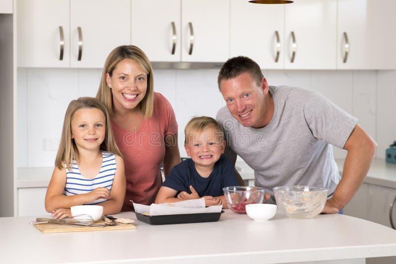 Ung lycklig parbakning samman med hemmastatt kök för liten son som och för ung härlig dotter har gyckel som spelar med kräm fotografering för bildbyråer