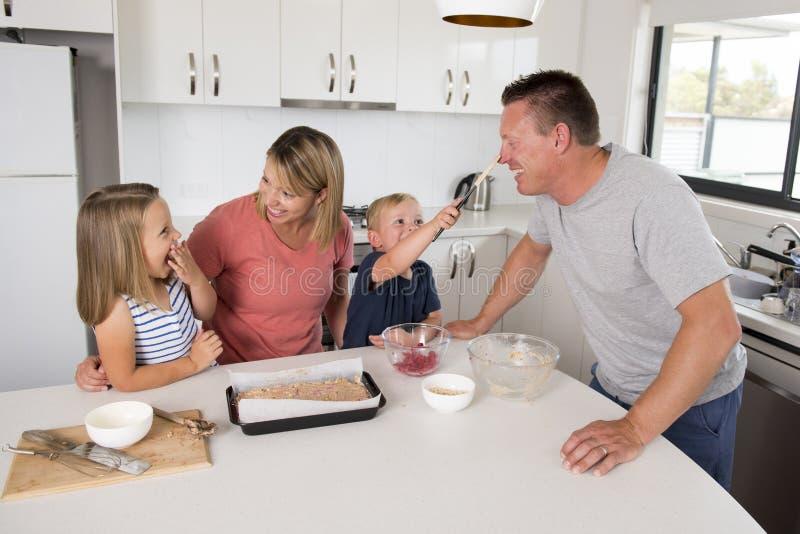 Ung lycklig parbakning samman med hemmastatt kök för liten son som och för ung härlig dotter har gyckel som spelar med kräm arkivbilder