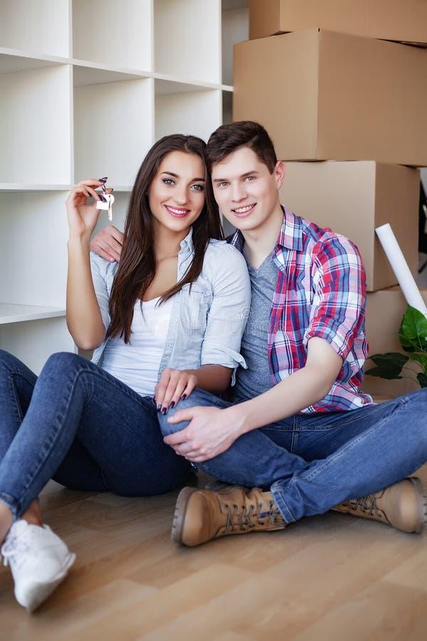 Ung lycklig parflyttning in i deras nya hem Dem som packar upp, och reng?rande nytt hem royaltyfri foto