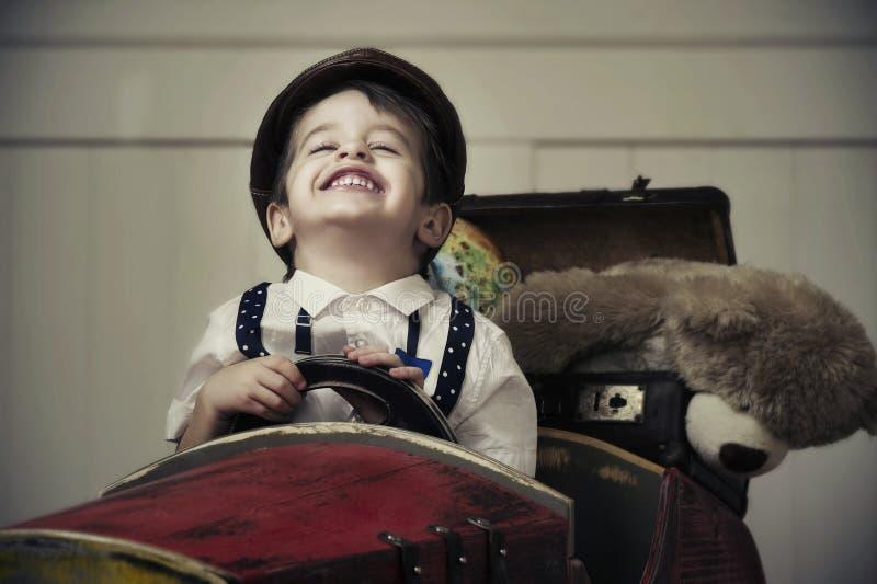Ung lycklig pojke i träbil arkivfoto