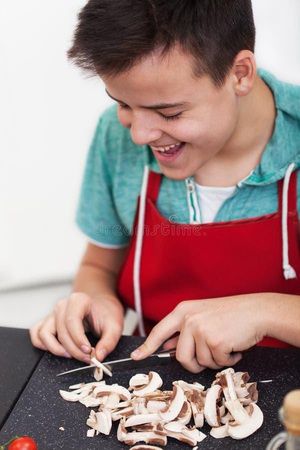 Ung lycklig pojke som förbereder en maträtt i köket - skivachampinjoner på skärbräda royaltyfria foton
