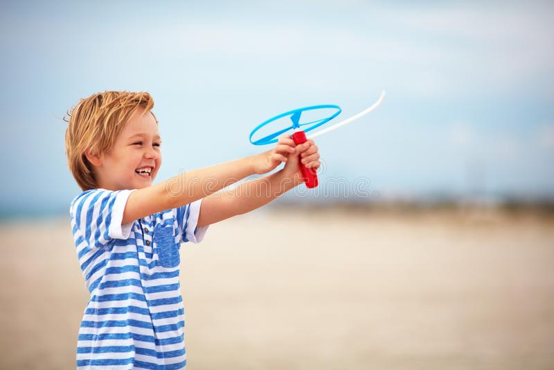 Ung lycklig pojke, unge som lanserar en leksakpropeller och att ha gyckel på sommarstranden royaltyfria bilder