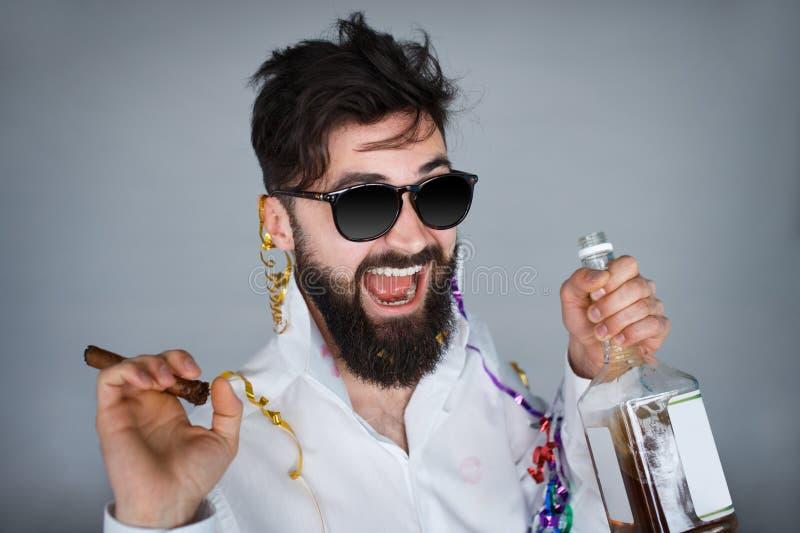 Ung lycklig skäggig man som har en drink på grå bakgrund royaltyfri bild