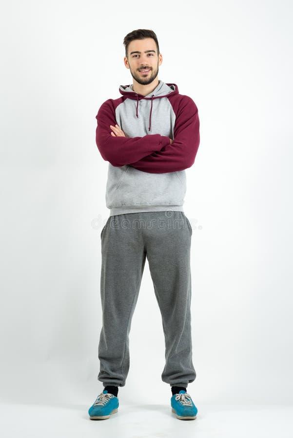 Ung lycklig skäggig tillfällig man i sportswear med korsade händer royaltyfri foto