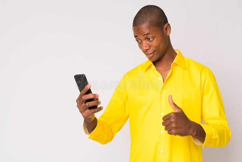 Ung lycklig skallig afrikansk affärsman som använder telefonen och ger upp tummar arkivbilder
