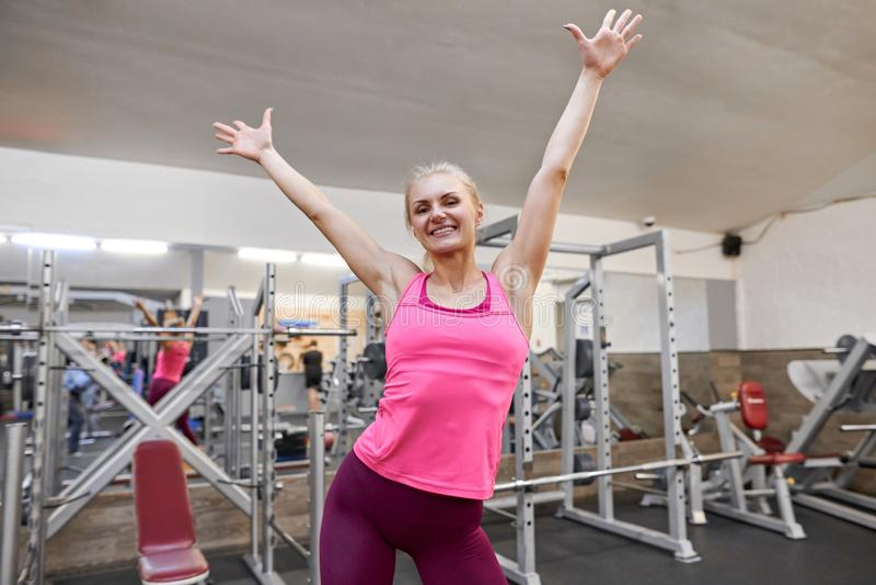 Ung lycklig sportig kvinna som lyfter hennes händer upp i idrottshall Begrepp för folkkonditionsport royaltyfri bild