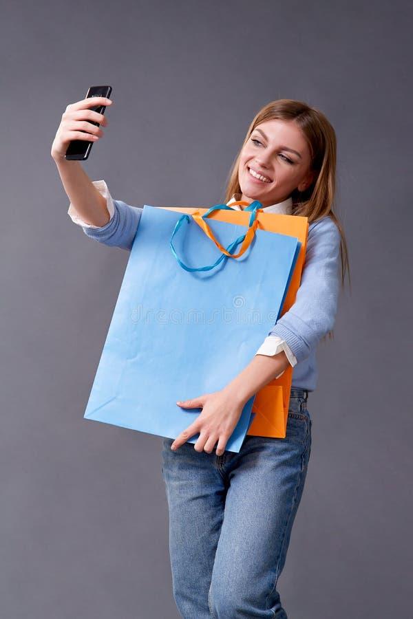 Ung lycklig studentflicka med packar som sitter p? golvet arkivbild