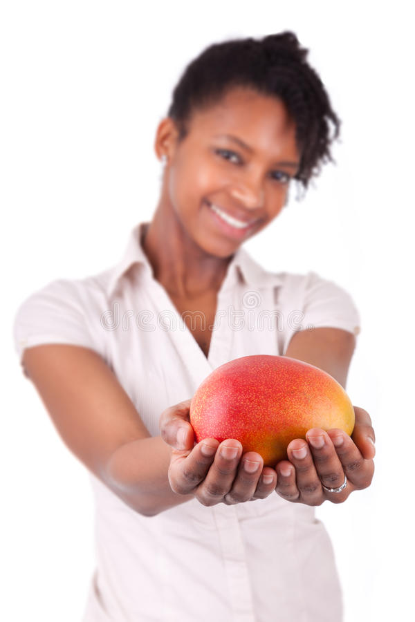 Ung lycklig svart-/afrikansk amerikankvinna som rymmer den nya mango royaltyfri foto