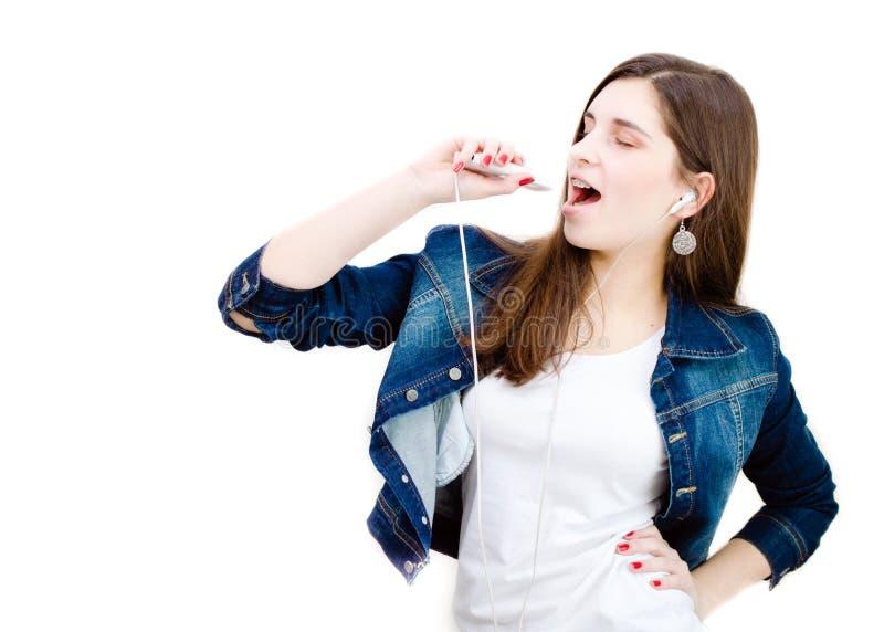 Ung lycklig tonårs- flicka som sjunger med musikspelaren på vit bakgrundscopyspace royaltyfri fotografi