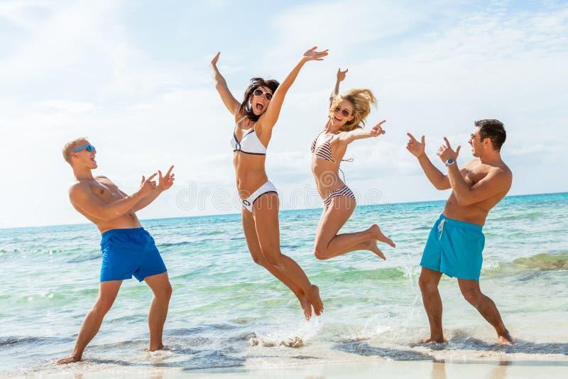 Ung lycklig vänhavingyckel på stranden royaltyfri bild