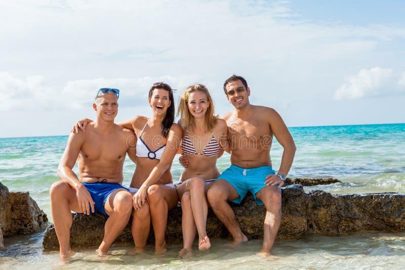 Ung lycklig vänhavingyckel på stranden fotografering för bildbyråer