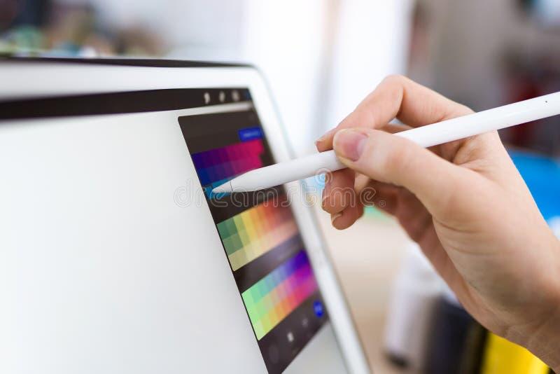 Ung märkes- kvinnahand som arbetar med hennes digitala minnestavla på kontoret arkivbilder