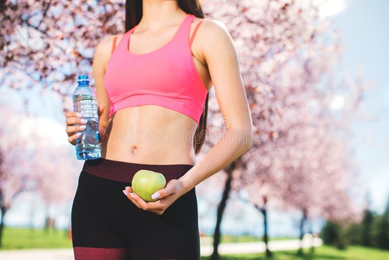 Ung mager kvinna som rymmer det gröna äpplet och flaskan av vatten Kondition och sunt livsstilbegrepp royaltyfria bilder