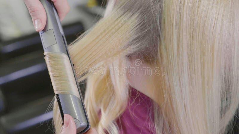 Ung makeupkonstnär som applicerar läppstift på kanter för modell` s arkivbild