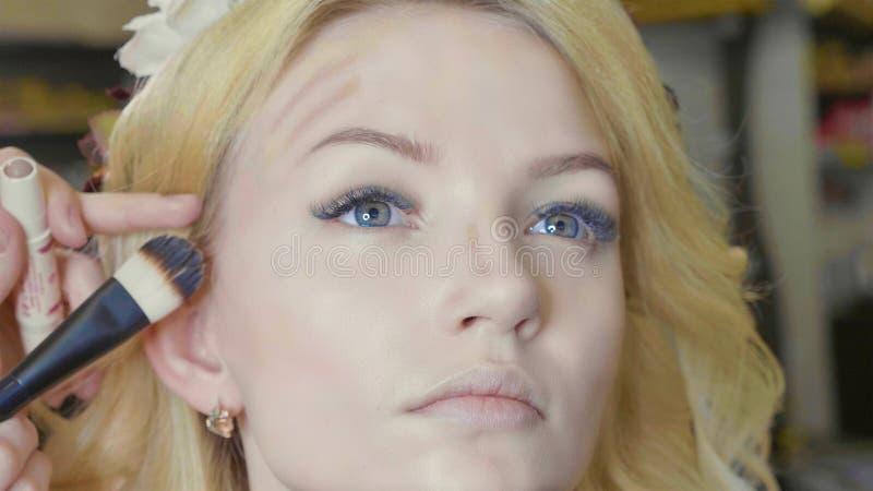 Ung makeupkonstnär som applicerar täckstift på framsida för modell` s royaltyfria foton