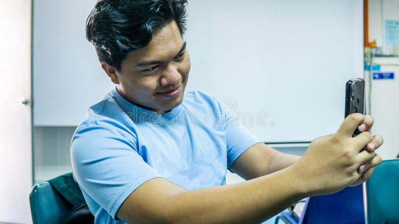 Ung Malay man ler och tar en selfie med sin smartphone royaltyfria foton