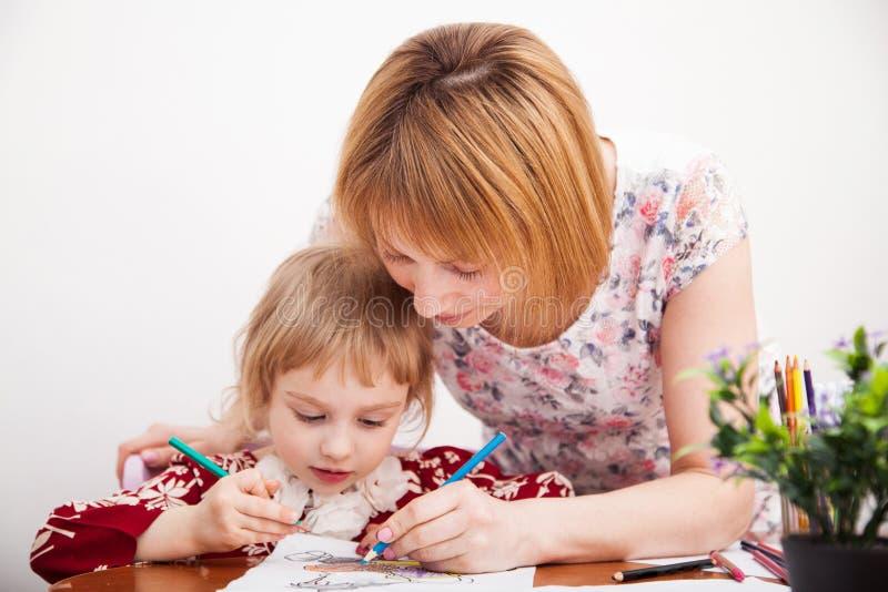 Ung mamma och hennes lilla dotterteckning royaltyfria foton
