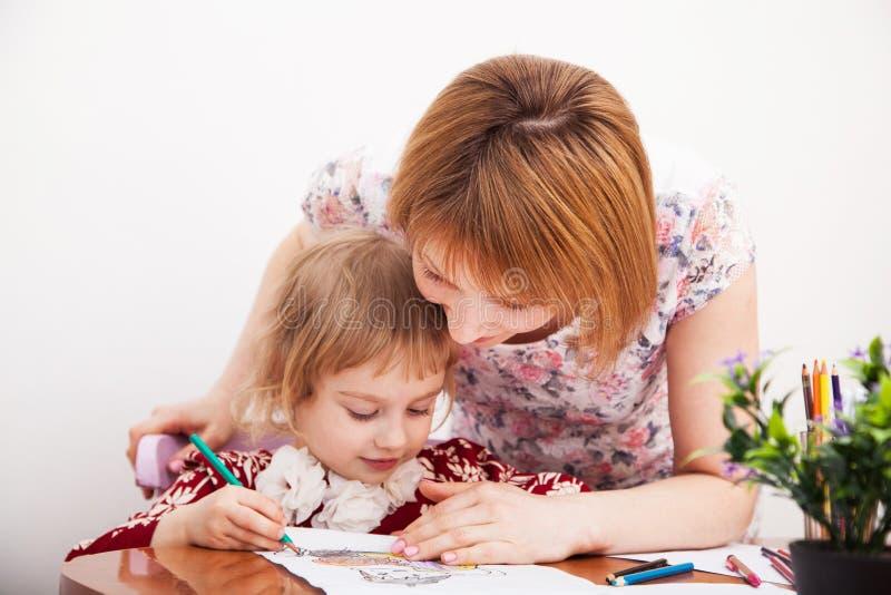 Ung mamma och hennes lilla dotterteckning royaltyfri bild