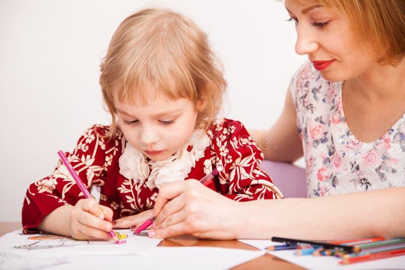 Ung mamma och hennes lilla dotterteckning royaltyfria bilder