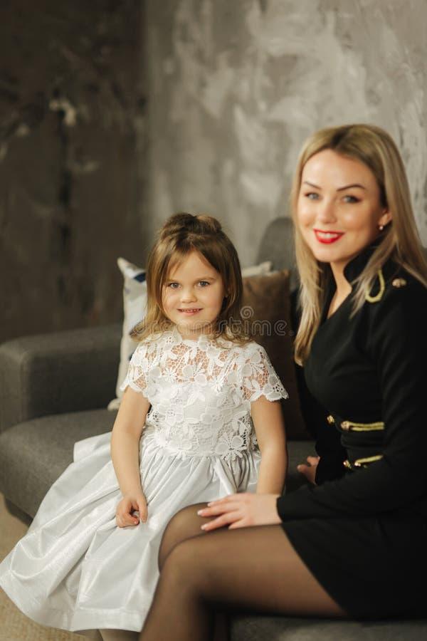 Ung mamma och liten dotter hemma som sitter på soffan Attraktiv moder i svart klänning lycklig familj royaltyfri fotografi