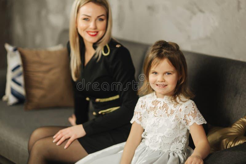 Ung mamma och liten dotter hemma som sitter på soffan Attraktiv moder i svart klänning lycklig familj royaltyfria bilder