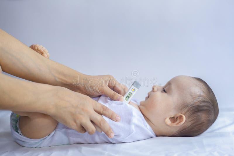 Ung mamma som mäter temperatur av den lilla sjuka pojken Använda termometern royaltyfria foton