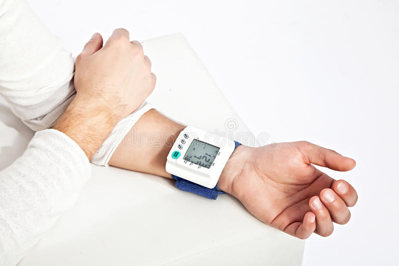Ung man'shand som mäter hans blodtryck royaltyfria bilder