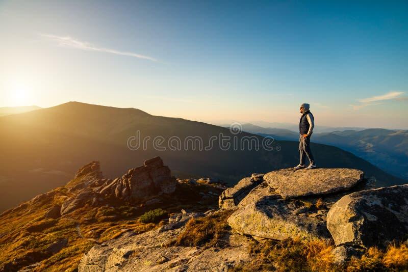 Ung man överst av ett berg som håller ögonen på solnedgången arkivfoto