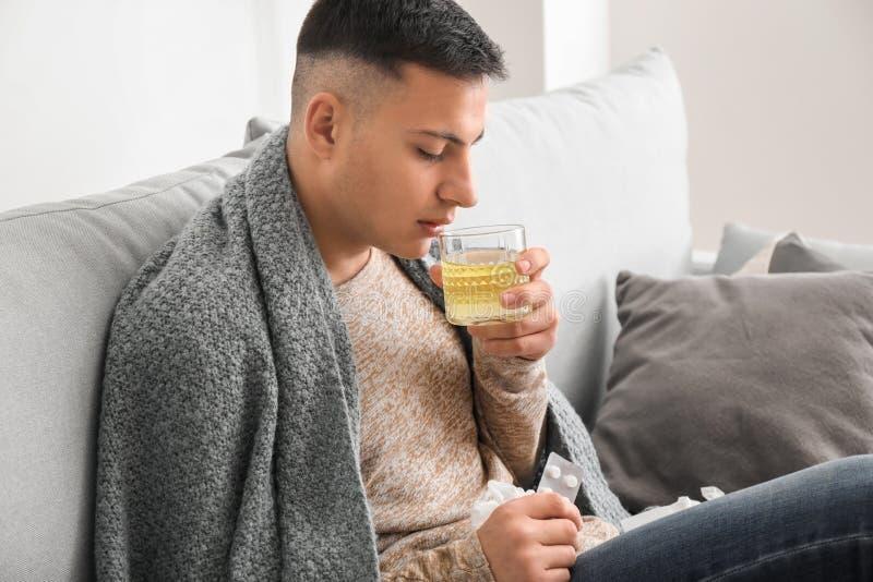 Ung man dåligt med influensa som hemma tar medicin arkivbild
