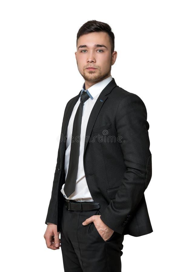 Ung man en affärsdräkt, händer i hans fack som isoleras på vit bakgrund royaltyfria foton