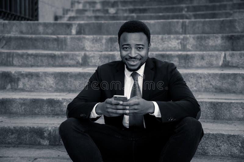 Ung man för affärsentreprenör som utomhus sitter stads- trappa som arbetar och använder den smarta telefonen fotografering för bildbyråer