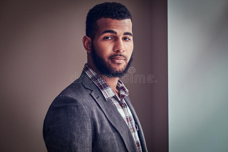 Ung man för afrikansk amerikan som ser en kamera i en studio fotografering för bildbyråer