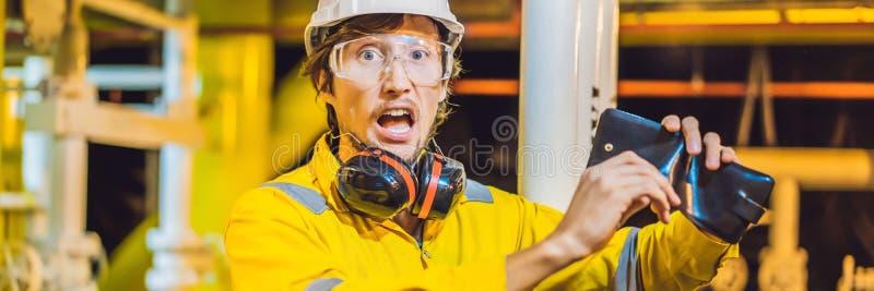 Ung man för BANER, för LÅNGT FORMAT i en gul arbetslikformig, exponeringsglas och hjälm i bruksmiljön, oljaplattform eller arkivfoton