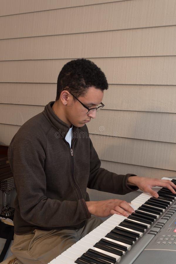 Ung man för blandat lopp som spelar ett elektriskt tangentbord, placerad neutral bakgrund royaltyfri fotografi