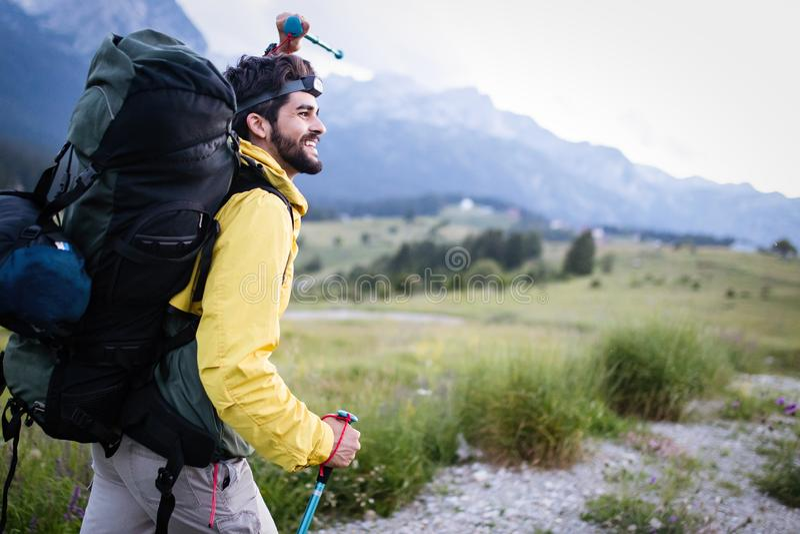 Ung man f?r fotvandrare med ryggs?cken och trekking poler som ser bergen i utomhus- royaltyfria foton