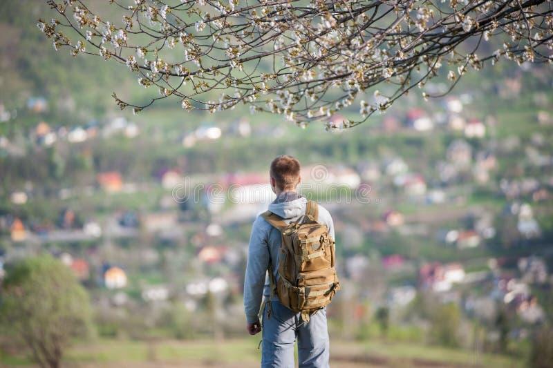 Ung man för handelsresande med ryggsäcken på kullen fotografering för bildbyråer