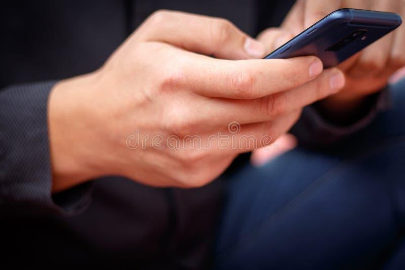 ung man för livsstil som använder på en mobiltelefon med det smsande meddelandet royaltyfria foton