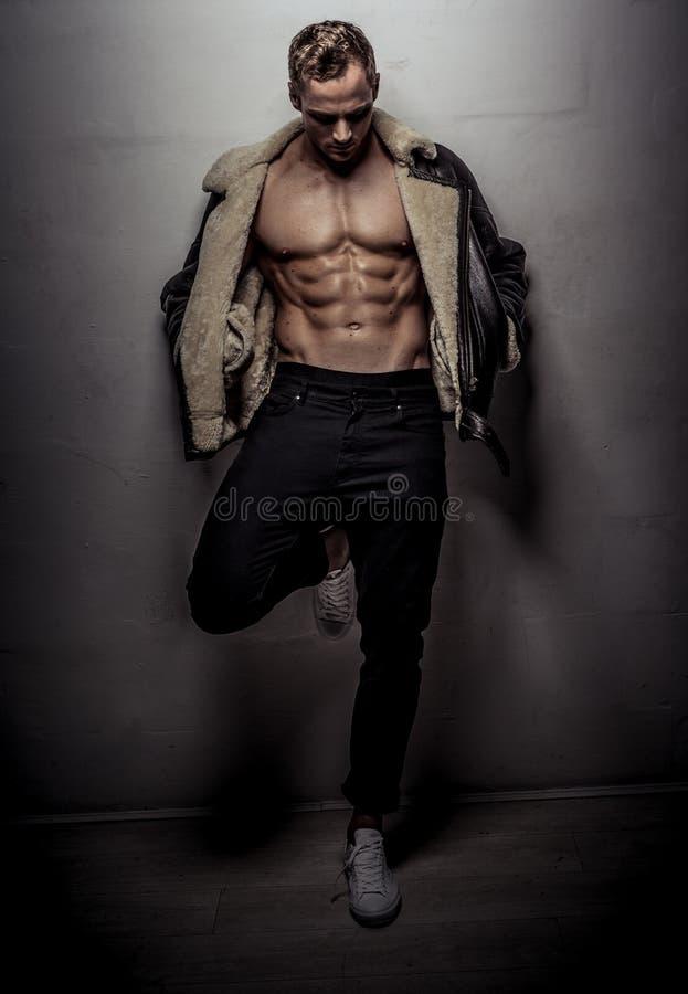 Ung man för muskulös idrottsman nen som poserar över ljus - grå vägg royaltyfria bilder