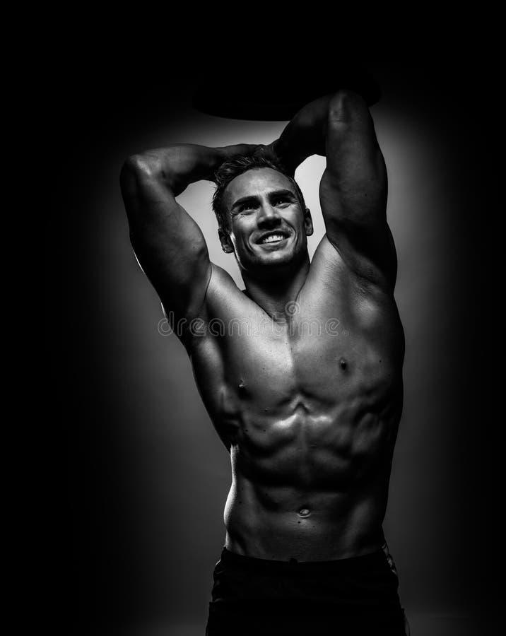 Ung man för muskulös idrottsman nen som poserar i svartvit studio arkivfoto