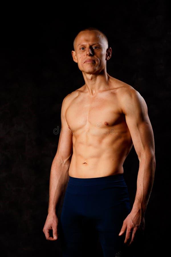 Ung man för muskulösa modellsportar på en mörk bakgrund Stående av den sportiga sunda starka muskelgrabben sexig torso royaltyfri foto
