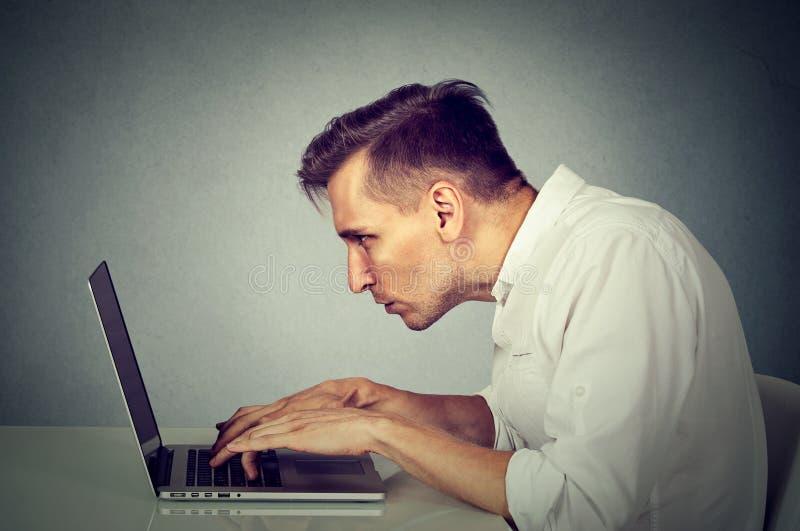 Ung man för sidoprofil som arbetar på datorsammanträde på skrivbordet royaltyfria bilder