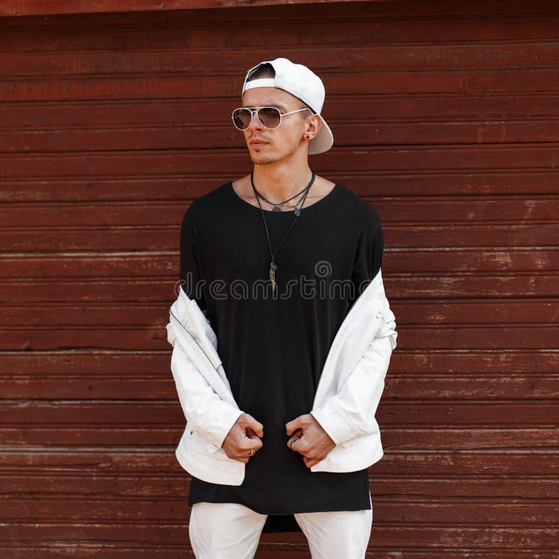 Ung man för stilig hipster i ett trendigt vitt sommaromslag i en stilfull svart t-skjorta i en moderiktig baseballmössa royaltyfri foto