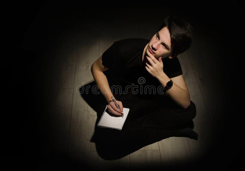 Ung man för tonåring som tänker och skriver på anteckningsboken på svartbac royaltyfria foton