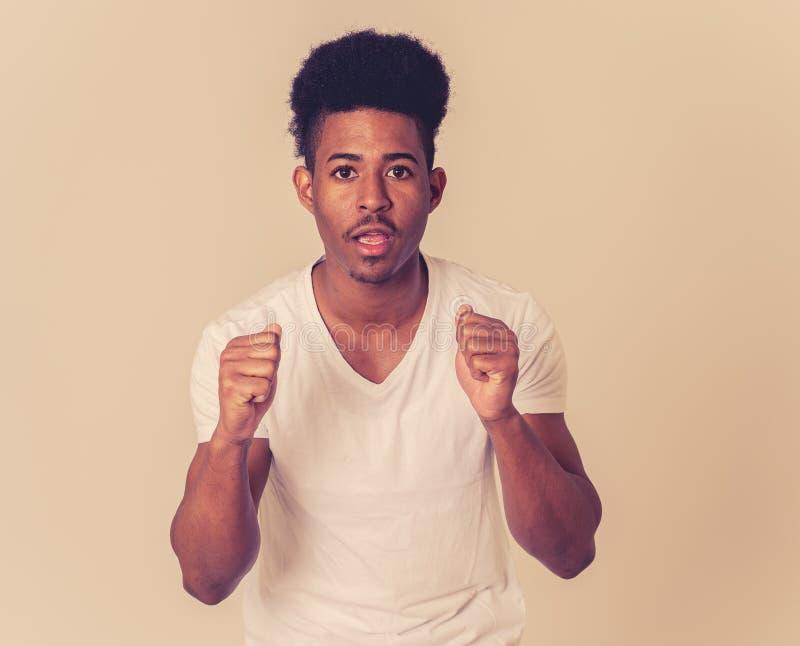 Ung man f?r ung afrikansk amerikan som ser skr?md och chockad p? n?got m?nskliga uttryck arkivfoto