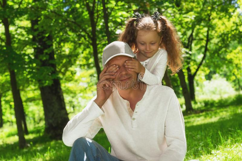 Ung man f?r n?ra ?vre st?ende med st?ngda ?gon inomhus Lycklig gladlynt liten dotter som spelar täcka pappaögon med händer royaltyfria foton