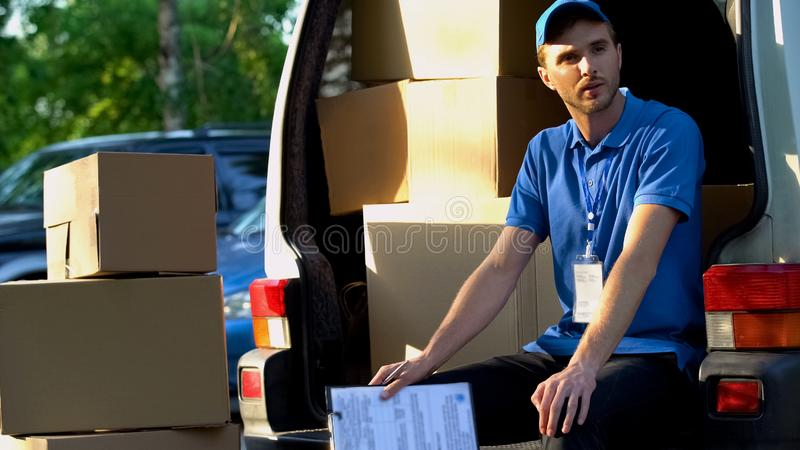 Ung man från hemsändning som vilar och att sitta i skåpbil, ladda av jordlotter royaltyfria foton