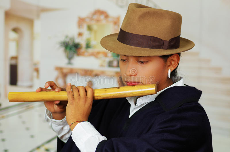 Ung man från Otavalo, Ecuador som spelar quenaflöjten royaltyfri foto