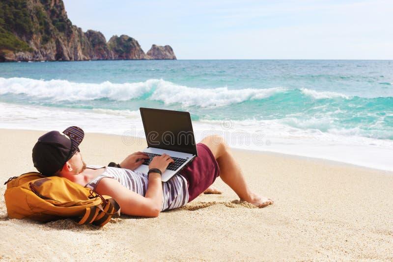Ung man i ärmlös tröja, kortslutningar, snapbacklock på stranden med bärbara datorn & ryggsäck Freelancer hipsterblogger, författ royaltyfria bilder