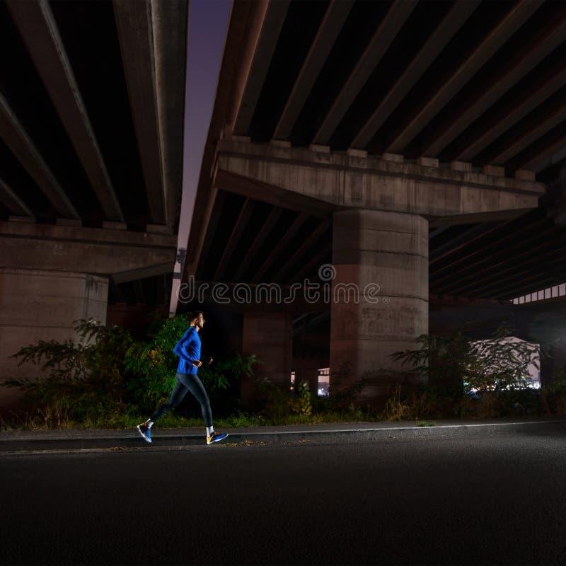 Ung man i blå spring på natten running stads- Sund livsstil och sportbegrepp arkivfoton
