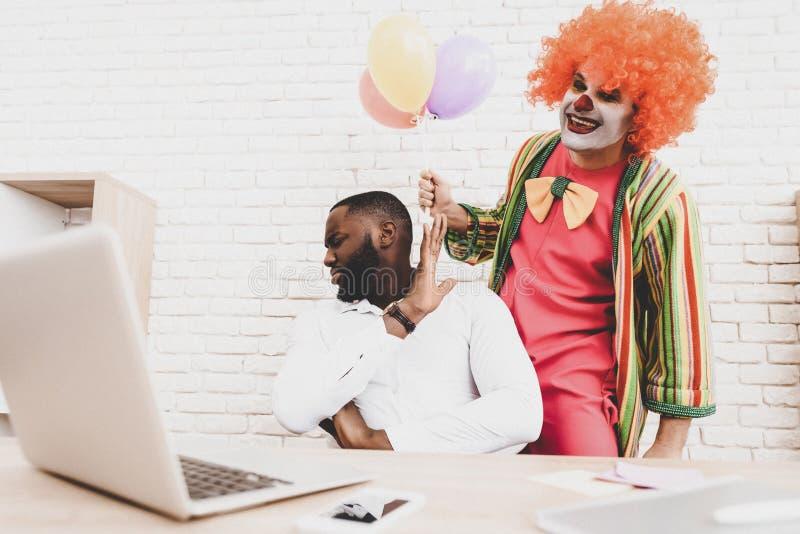 Ung man i clownen Costume med Baloons i regeringsställning royaltyfria bilder